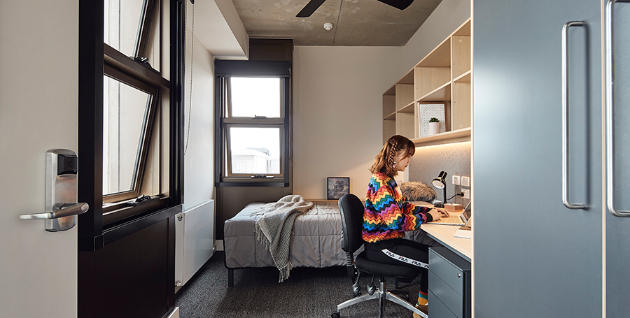 Student studying in bedroom at Brougham House, Geelong Waterfront Campus
