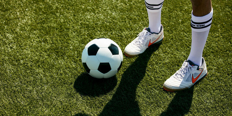 Soccer ball on soccer field next to a soccer player's feet