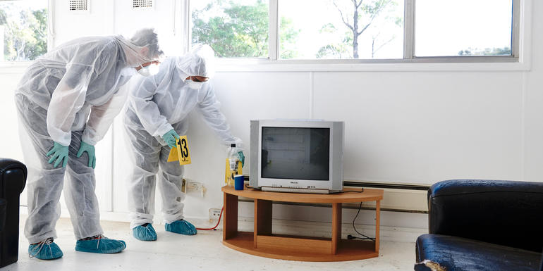 Forensic scientists analysing evidence in crime scene house