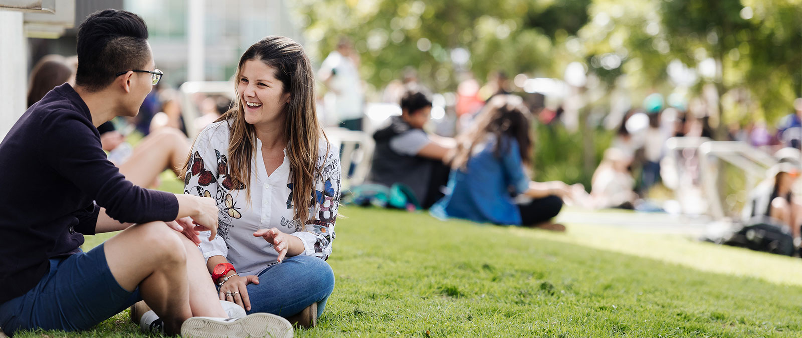 Colombian student laughing with other student sitting on the grass