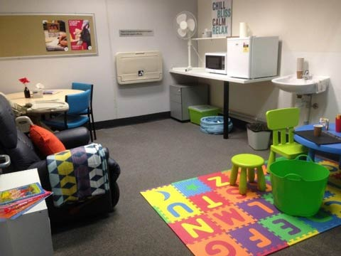 Parent room with table and chairs, comfy nursing chair, change table, microwave, fridge, sink and colourful play area