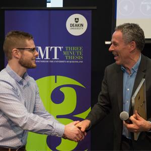 Deputy Vice-Chancellor Global Engagement Professor Gary Smith (right) presents Deakin's 3MT winner, Jarrod Hogan with his award.