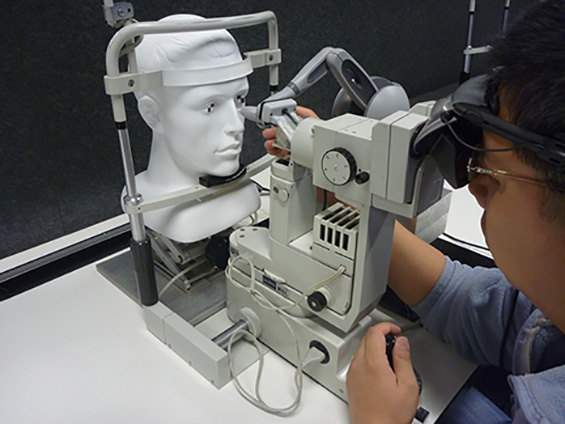 A researcher demonstrates the haptic device. They peer into the slit lamp and their hand holds the stylus of the device, which examines a human model's face.