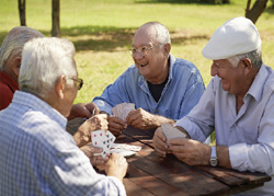 an image of four older gentleman playing cards