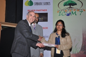 Dr Alok Adholeya (centre) looks on proudly as Leena Johny (right) is presented with her prize.