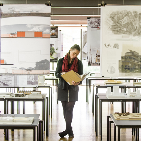 Student standing amongst Architecture exhibition looking through a folio