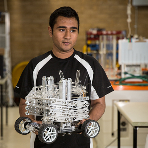 Student holding robot created for the Warman Design and Build Competition