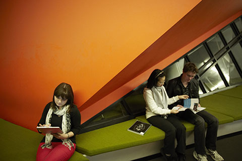 Students using tablet and reading brochure